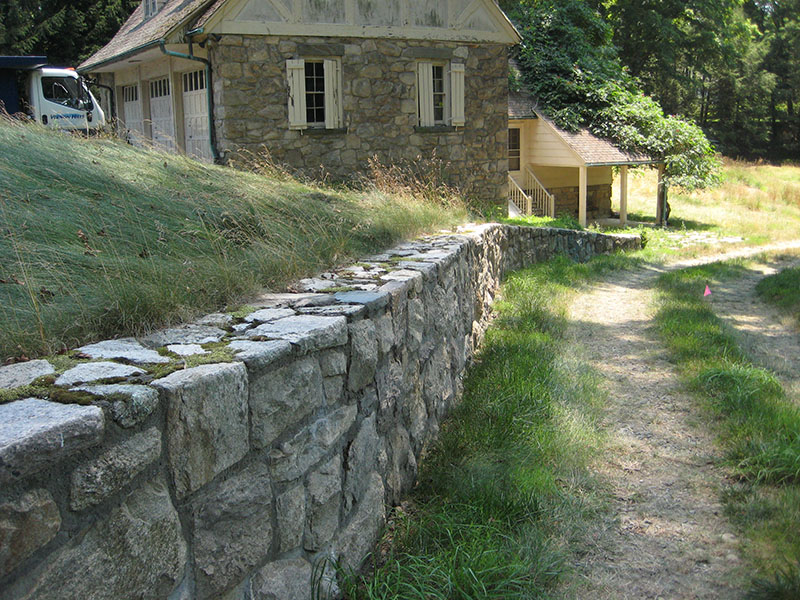 stone wall with barn in background