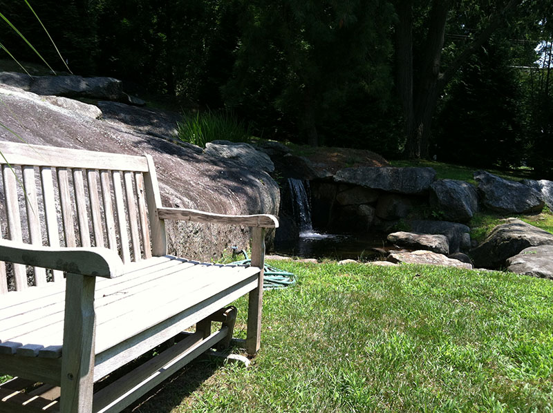 wooden bench with creek waterfall
