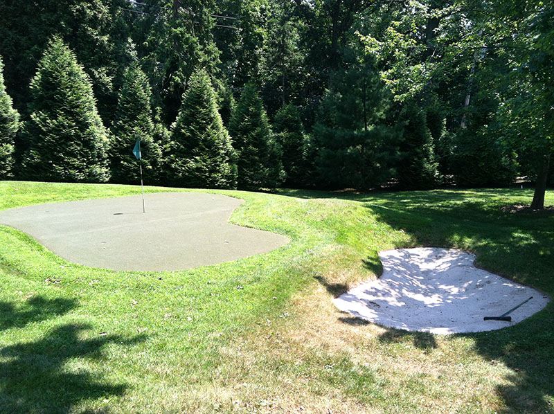 putting green and sand trap in backyard