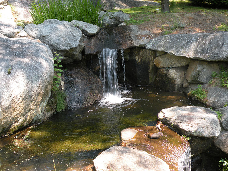 Miniature waterfall near pool