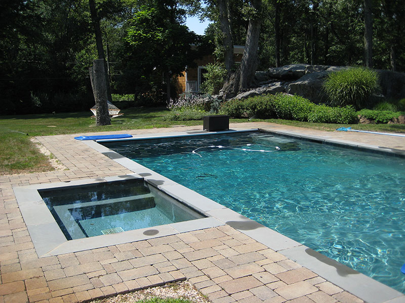 large swimming pool with stone patio